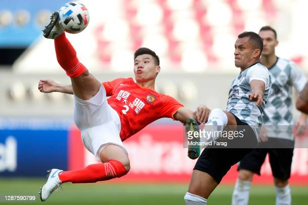 Dyanfres Douglas of Vissel Kobe and Mei Fang of Guangzhou Evergrande compete for the ball during the AFC Champions League Group G match between...