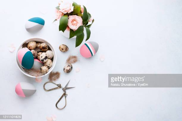 dyed quail egg and color easter eggs lying in tray on wihte table with feather and pink roses. - happy easter in russian stock pictures, royalty-free photos & images