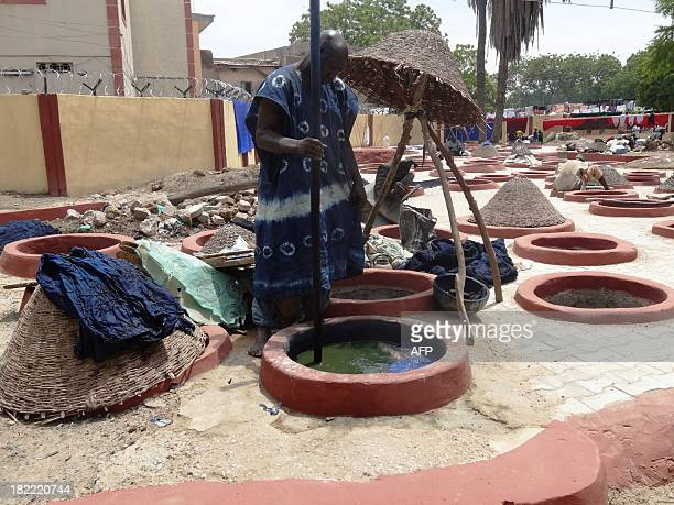 A dyer stirs dye solution in a sixfoot indigo dye pit as part of a traditional indigo dyeing process at the 500 years old Kofar Mata dye pits in the...