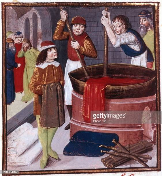 Dyers immersing bolt of cloth in vat of dye placed over a fire At bottom right is bundle of sticks ready to be added to fire15th century manuscript...
