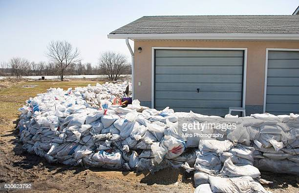 dyke of sandbags around rural home to protect from red river floodwaters, rural manitoba - sandbag stock pictures, royalty-free photos & images