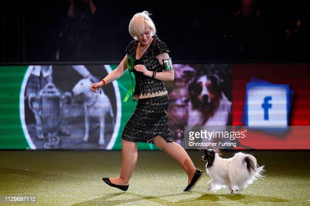Dylan, a Papillon from Belgium, and owner Kathleen Roosens celebrate after winning Best in Show on the last day of Crufts Dog Show at the National...