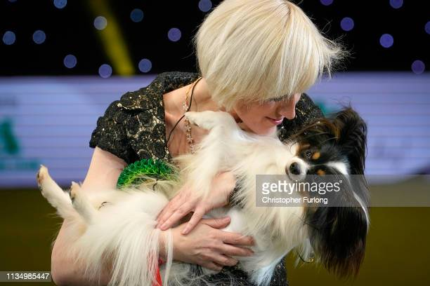 Dylan a Papillon from Belgium and owner Kathleen Roosens celebrate after winning Best in Show on the last day of Crufts Dog Show at the National...