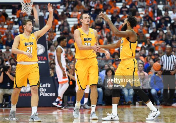 Dylan Alderson and Luke Knapke of the Toledo Rockets greet teammate Tre'Shaun Fletcher after a made basket against the Syracuse Orange during the...