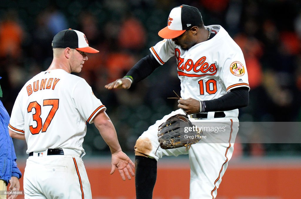 Dylan Bundy #37 of the Baltimore Orioles celebrates with Adam Jones #10 after throwing a complete game shutout against the Seattle Mariners at Oriole Park at Camden Yards on August 29, 2017 in Baltimore, Maryland.