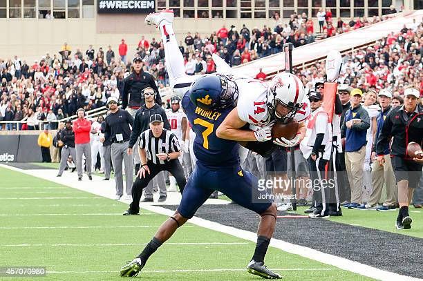 Dylan Cantrell of the Texas Tech Red Raiders comes down with the ball while being defended by Daryl Worley of the West Virginia Mountaineers on...