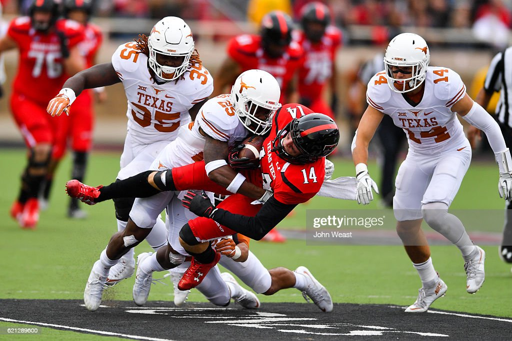Dylan Cantrell #14 of the Texas Tech Red Raiders is tackled by Antwuan Davis #25 of the Texas Longhorns during the game on November 5, 2016 at AT&T Jones Stadium in Lubbock, Texas. Texas defeated Texas Tech 45-37.
