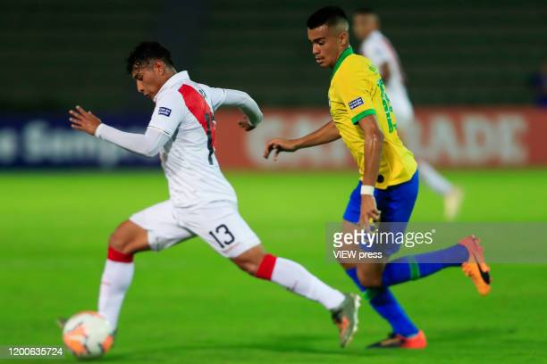 Dylan Caro of Peru fights for the ball against Reinier of Brazil during their CONMEBOL PreOlympic soccer game at Centenario Stadium on January 19...