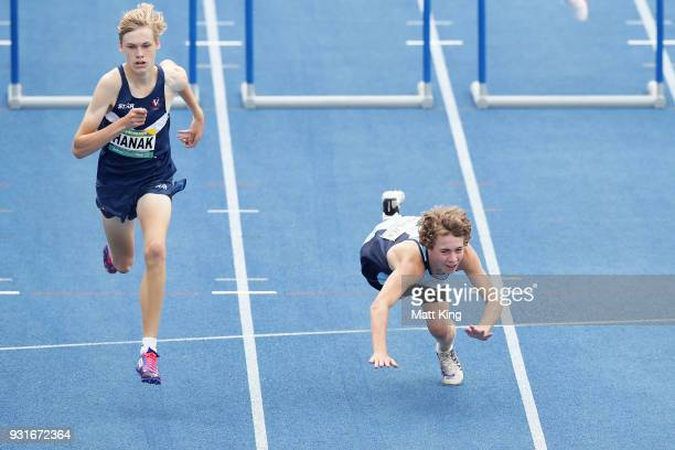 Dylan Charlier of NSW falls next to Hugo Hanak of QLD in the Men's under 15 200m hurdles preliminaries during day one of the Australian Junior...