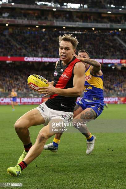 Dylan Clarke of the Bombers gathers the ball against Chris Masten of the Eagles during the round 14 AFL match between the West Coast Eagles and the...
