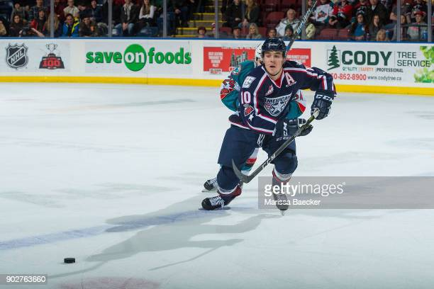 Dylan Coghlan of the TriCity Americans is back checked by Kyle Topping of the Kelowna Rockets as they skate over the blue line in pursuit of the puck...