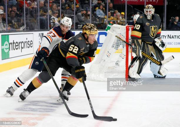 Dylan Coghlan of the Vegas Golden Knights skates with the puck against Warren Foegele of the Edmonton Oilers as Robin Lehner of the Golden Knights...