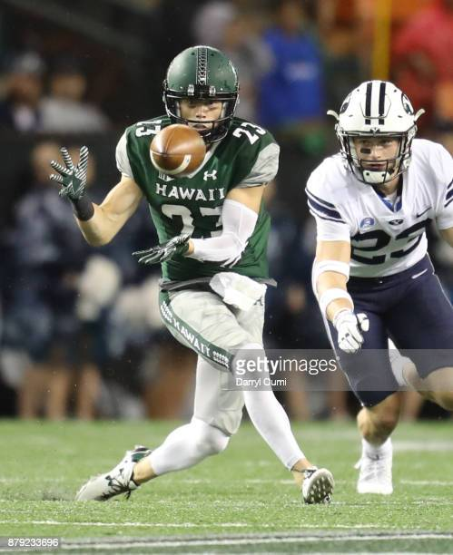 Dylan Collie of the Hawaii Rainbow Warriors concentrates as he attempts to catch a pass as he is guarded by Zayne Anderson of the BYU Cougars during...