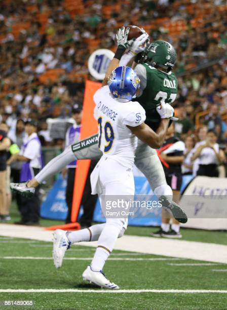 Dylan Collie of the Hawaii Rainbow Warriors makes a reception in the end zone as he is closely guarded by Dakari Monroe of the San Jose State...
