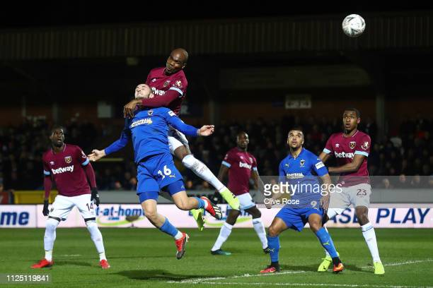 Dylan Connolly of AFC Wimbledon heads the ball under a challenge by Angelo Ogbonna of West Ham United during the FA Cup Fourth Round match between...