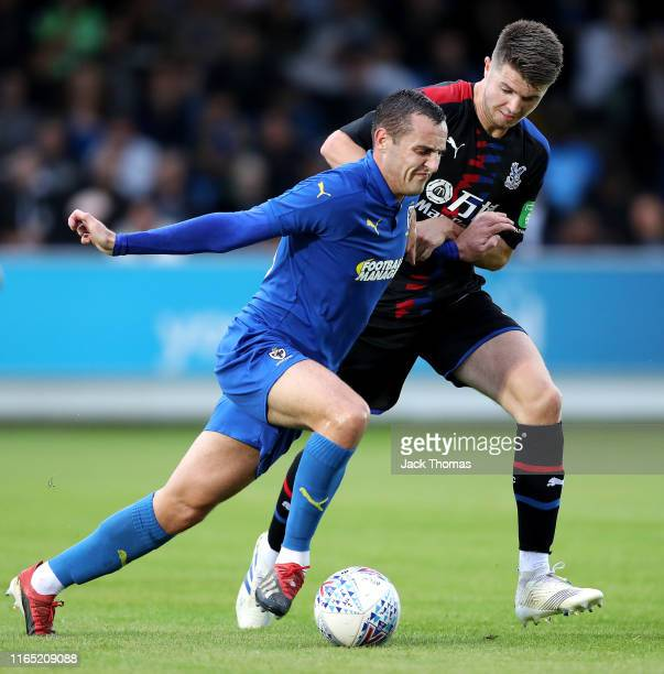 Dylan Connolly of AFC Wimbledon is challenged by Luke Dreher of Crystal Palace during the PreSeason Friendly match between AFC Wimbledon and Crystal...