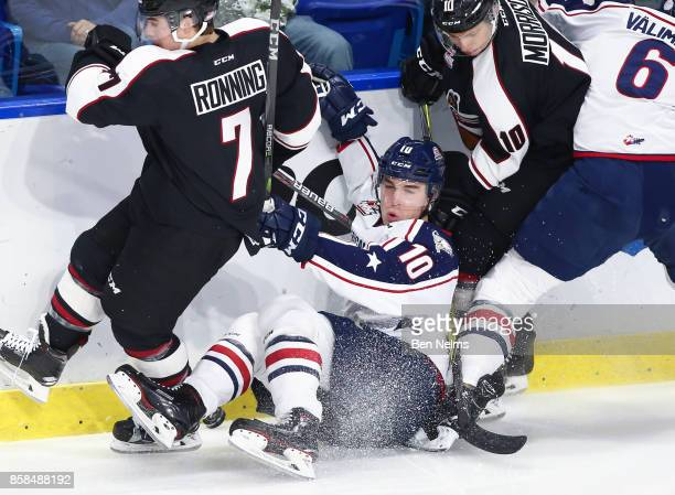 Dylan Coughlan of the TriCity Americans is checked by Ty Ronning of the Vancouver Giants during the first period of their WHL game at the Langley...