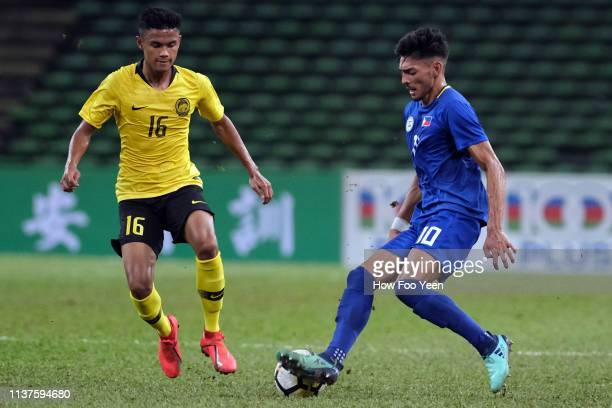 Dylan De Bruycker of the Phillipines tries to dribble past Muhammad Danial Amier of Malaysia during the AFC U23 Championship qualifier between...