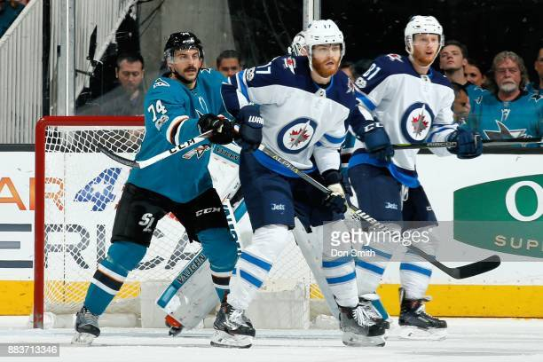 Dylan DeMelo and Martin Jones of the San Jose Sharks defend Adam Lowry and Kyle Conner of the Winnipeg Jets at SAP Center on November 25 2017 in San...