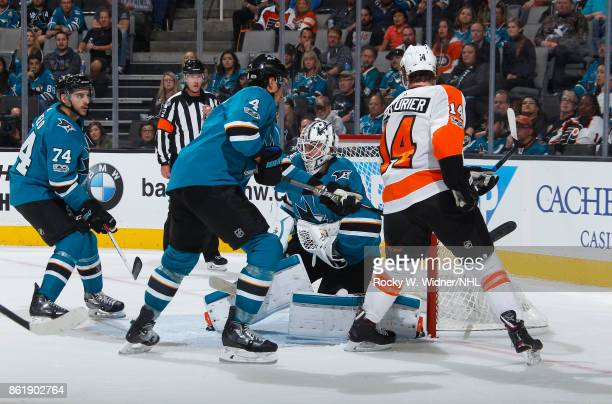 Dylan DeMelo Brenden Dillon and Martin Jones of the San Jose Sharks defend the net against Sean Couturier of the Philadelphia Flyers at SAP Center at...