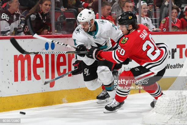 Dylan DeMelo of the San Jose Sharks and Brandon Saad of the Chicago Blackhawks chase the puck in the second period at the United Center on February...