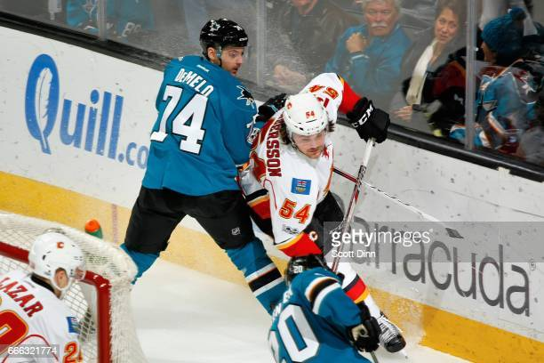 Dylan DeMelo of the San Jose Sharks and Rasmus Andersson of the Calgary Flames battle along the boards during a NHL game at SAP Center at San Jose on...