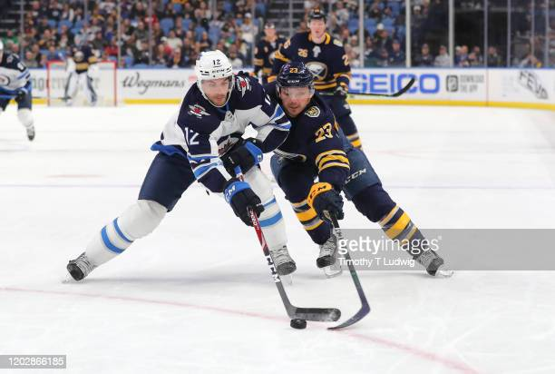 Dylan DeMelo of the Winnipeg Jets and Sam Reinhart of the Buffalo Sabres go after a loose puck during the second period at KeyBank Center on February...