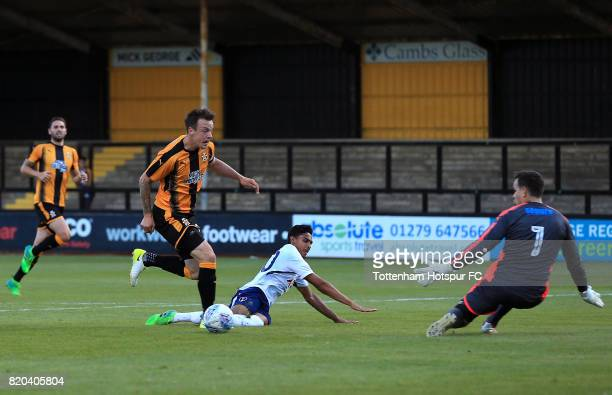 Dylan Duncan of Tottenham Hotspur passes under pressure from Josh Coulson and David Forde of Cambridge United to assist his sides second goal during...