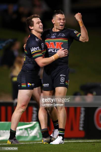 Dylan Edwards of the Panthers celebrates scoring a try with team mates Brent Naden of the Panthers during the round 12 NRL match between the Penrith...