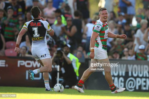 Dylan Edwards of the Panthers looks dejected as Damien Cook of the Rabbitohs celebrates scoring a try during the round two NRL match between the...