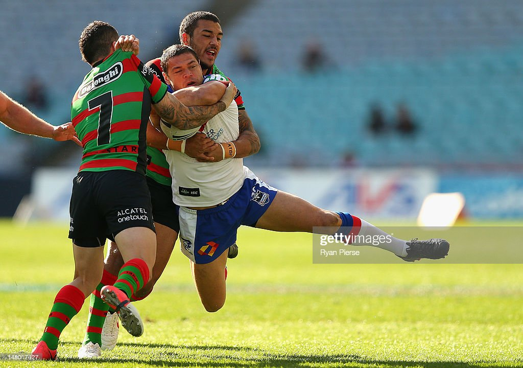 Dylan Farrell of the Rabbitohs tackles Timana Tahu of the Knights during the round 18 NRL match between the South Sydney Rabbitohs and the Newcastle Knights at ANZ Stadium on July 8, 2012 in Sydney, Australia.