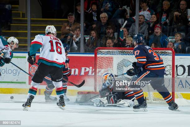 Dylan Ferguson of the Kamloops Blazers makes a third period save as Kole Lind of the Kelowna Rockets looks for the rebound on December 27 2017 at...