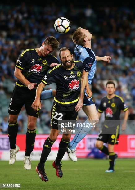 Dylan Fox and Andrew Durante of Wellington Phoenix compete with Matthew Simon of Sydney FC during the round 19 ALeague match between Sydney FC and...