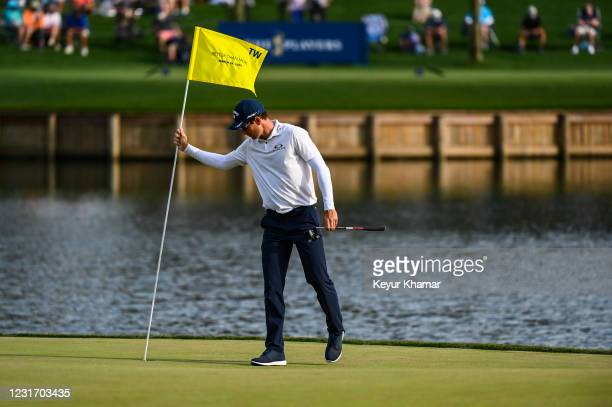 Dylan Frittelli of South Africa holds a pin flag with the text Better Than Most to commemorate a putt by Tiger Woods on the 17th hole green during...