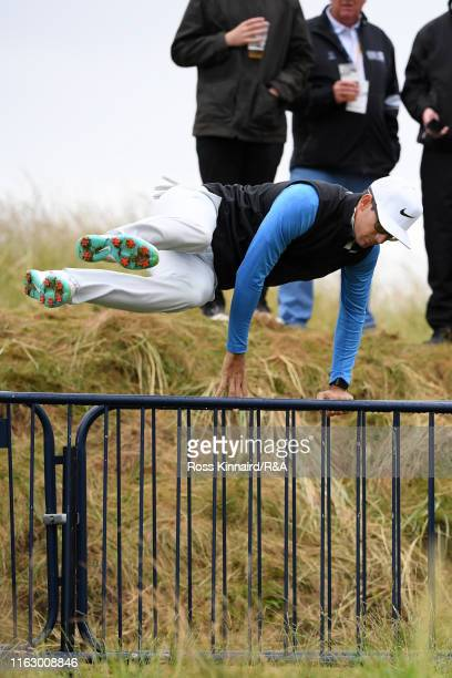 Dylan Frittelli of South Africa jumps over the barriers after checking on his ball on the seventeenth hole during the second round of the 148th Open...