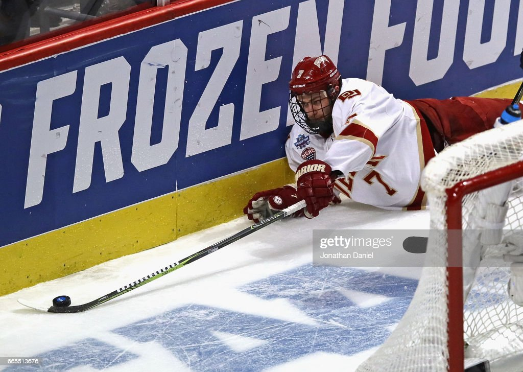 Dylan Gambrell #7 of the Denver Pioneers reaches for the puck after hitting the ice against the Notre Dame Fighting Irish during game two of the 2017 NCAA Division I Men's Hockey Championship Semifinal at the United Center on April 6, 2017 in Chicago, Illinois. Denver defeated Notre Dame 6-1.