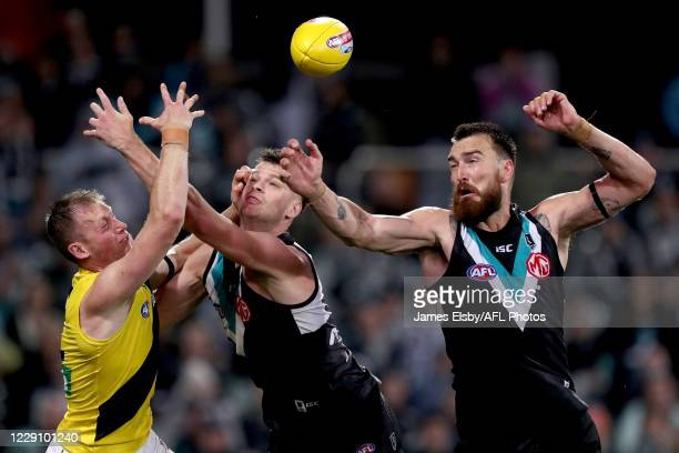 Dylan Grimes of the Tigers clashes with Peter Ladhams and Charlie Dixon of the Power during the 2020 AFL First Preliminary Final match between the...