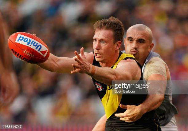 Dylan Grimes of the Tigers is tackled by Sam Powell-Pepper of the Power during the round 18 AFL match between the Richmond Tigers and the Port...