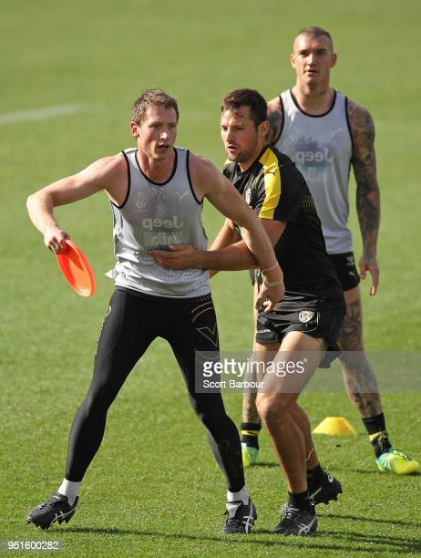 Dylan Grimes of the Tigers is tackled by Toby Nankervis of the Tigers as they play a game with a frisbee during the Richmond Tigers AFL training...