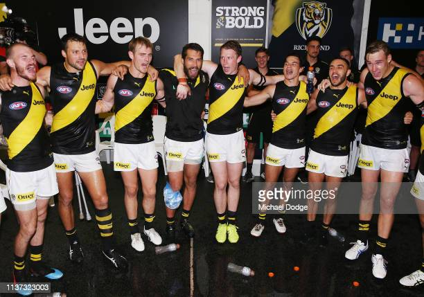 Dylan Grimes of the Tigers sing the club song after winning with1 Alex Rance of the Tigers who sustained a leg injury during the round one AFL match...