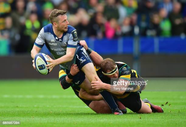 Dylan Hartley and Gareth Denman of Northampton Saints tackle Jack Carty of Connacht during Champions Cup Playoff match between Northampton Saints and...