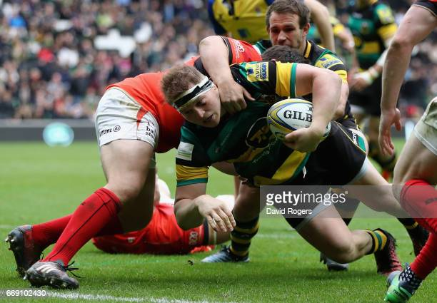 Dylan Hartley of Northampton dives over for a try despite being held by Jamie George during the Aviva Premiership match between Northampton Saints...