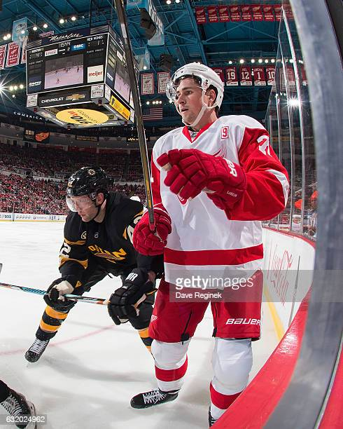 Dylan Larkin of the Detroit Red Wings battles along the boards with David Backes of the Boston Bruins during an NHL game at Joe Louis Arena on...