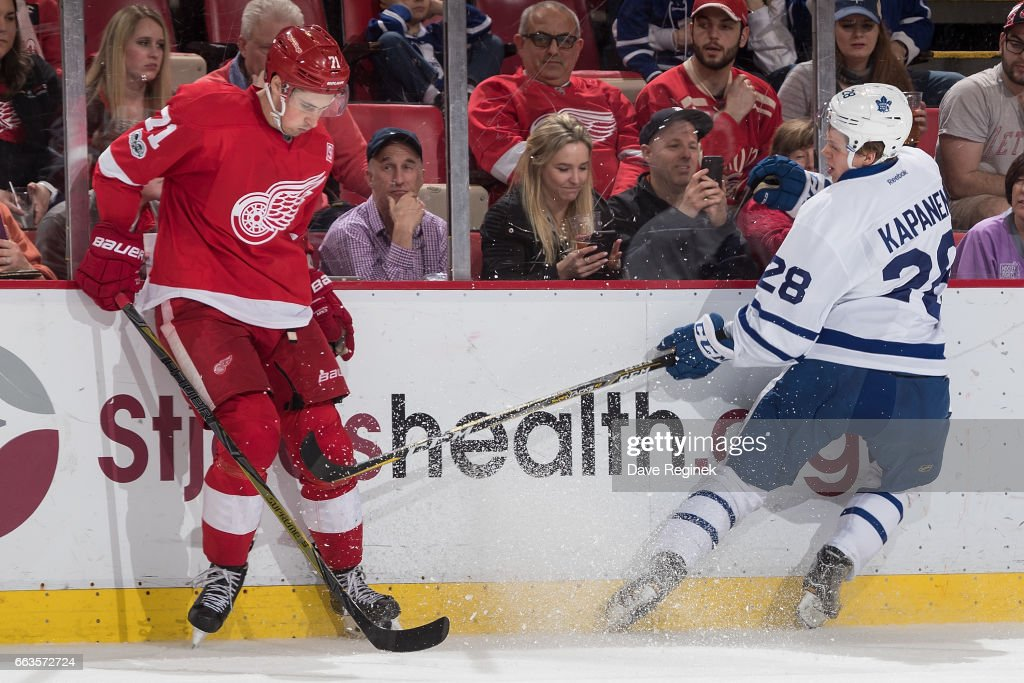Dylan Larkin #71 of the Detroit Red Wings battles along the boards with Kasperi Kapanen #28 of the Toronto Maple Leafs during an NHL game at Joe Louis Arena on April 1, 2017 in Detroit, Michigan. The Leafs defeated the Wings 5-4.