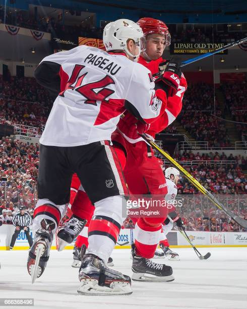 Dylan Larkin of the Detroit Red Wings battles for position with JeanGabriel Pageau of the Ottawa Senators during an NHL game at Joe Louis Arena on...