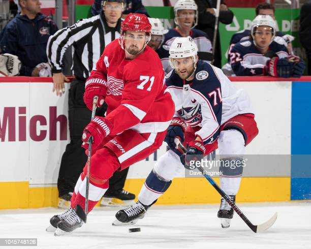 Dylan Larkin of the Detroit Red Wings battles for the puck with Nick Foligno of the Columbus Blue Jackets during an NHL game at Little Caesars Arena...