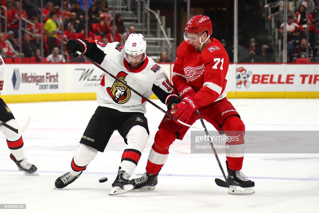 Dylan Larkin #71 of the Detroit Red Wings battles for the puck with Tom Pyatt #10 of the Ottawa Senators during the first period at Little Caesars Arena on March 31, 2018 in Detroit, Michigan.