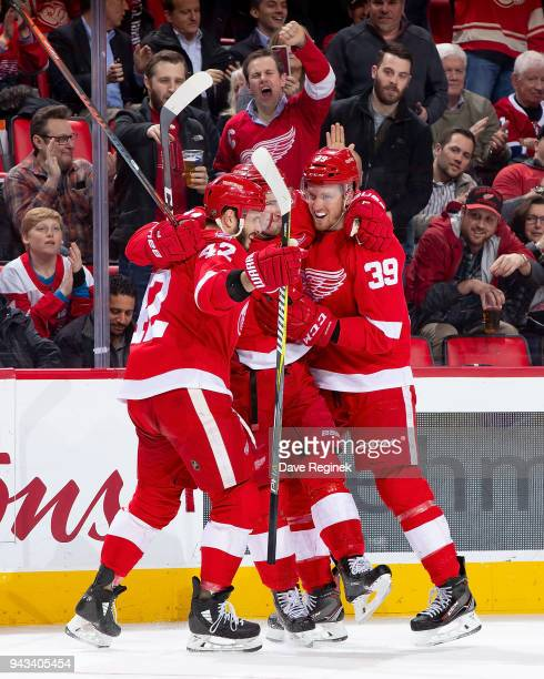 Dylan Larkin of the Detroit Red Wings celebrates a first period goal with teammates Andreas Athanasiou and Anthony Mantha during an NHL game against...