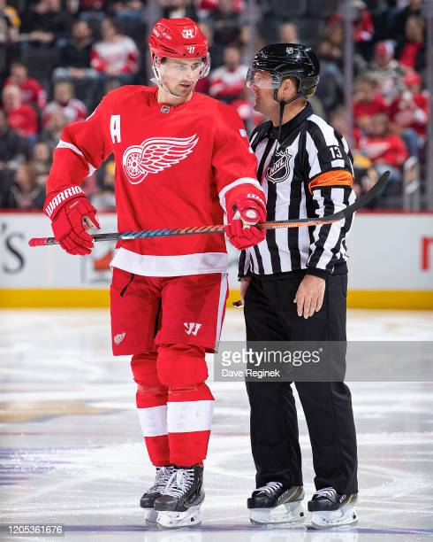 Dylan Larkin of the Detroit Red Wings chats with Referee Dan O'Halloran in his 1,500th NHL game before the start of the second period against the...