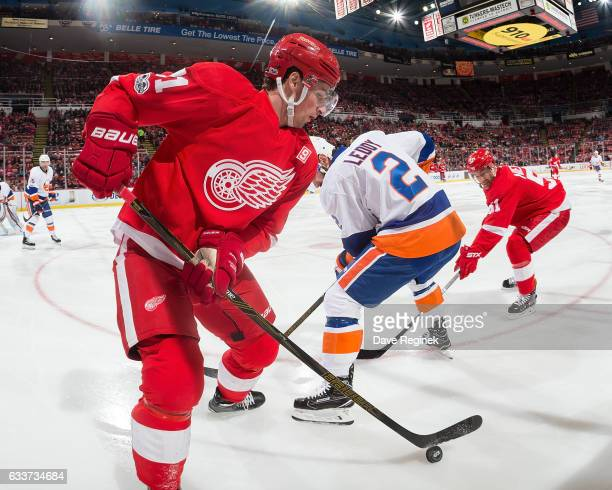 Dylan Larkin of the Detroit Red Wings controls the puck along the boards as teammate Frans Nielsen battles Nick Leddy of the New York Islanders...